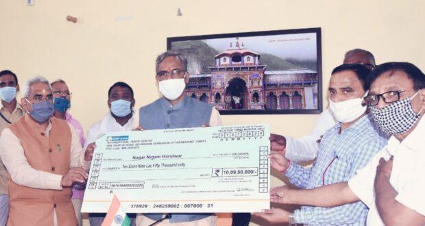 सीएम त्रिवेन्द्र सिंह रावत ने नगर निगम हरिद्वार को 10 करोड़ 9 लाख रुपये का चेक दिया